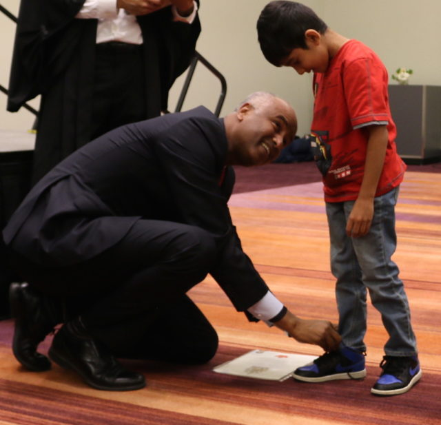 Immigration Minister Hussen helps new Canadian tie shoelace
